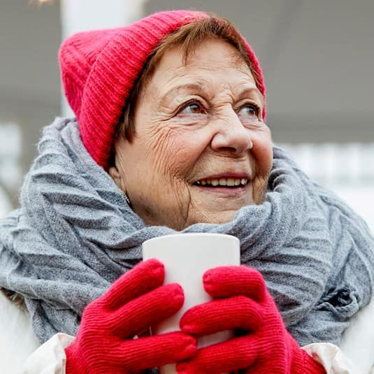A woman holding a cup of coffee, wearing a warm winter coat, hat, gloves and scarf